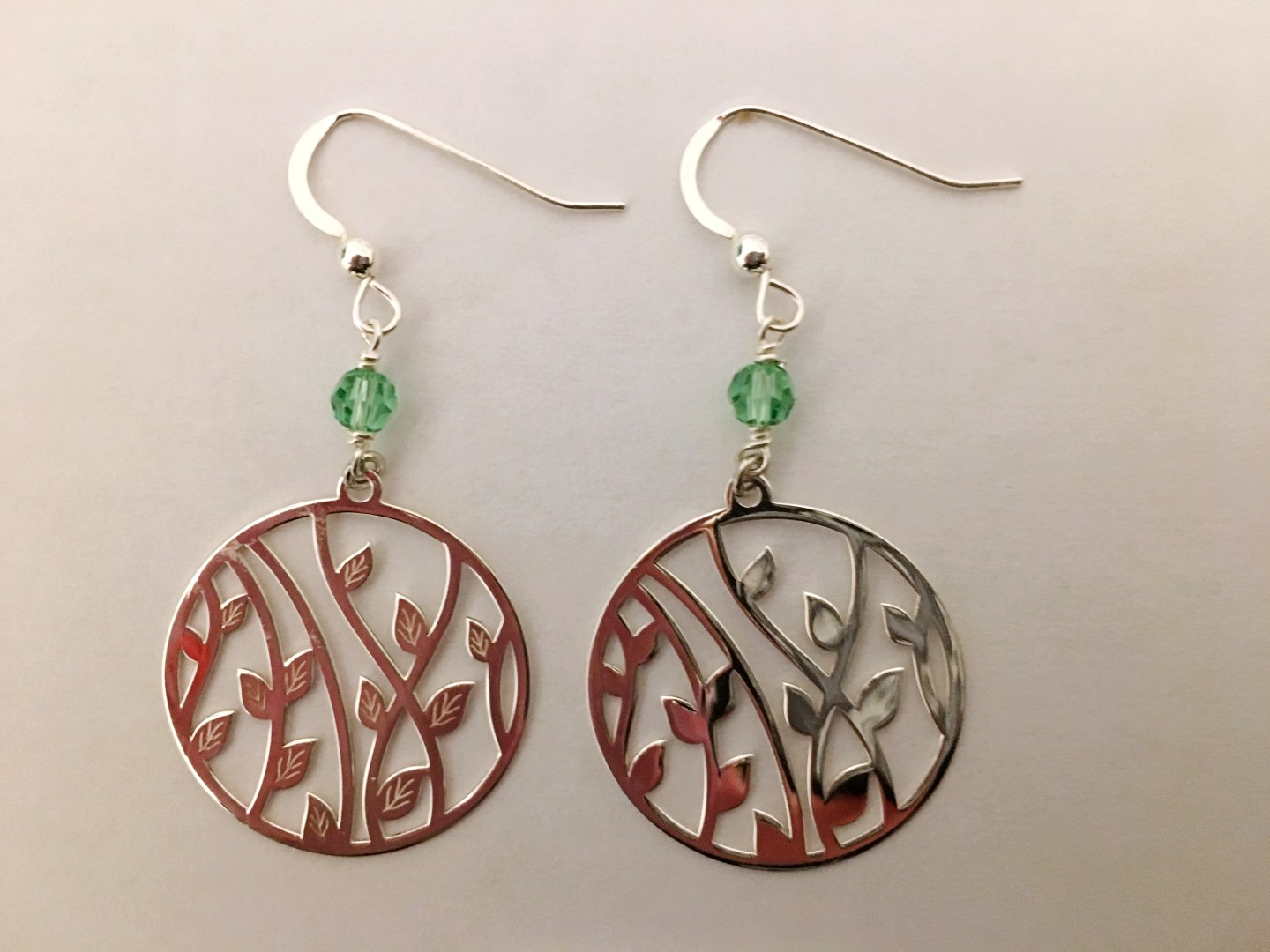 The sterling silver 'bamboo' drop earrings from House of Silver. They're for pierced ears, with fishhooks and a small drop with a green gem. Below this is the circle with a cut out leaf pattern design.