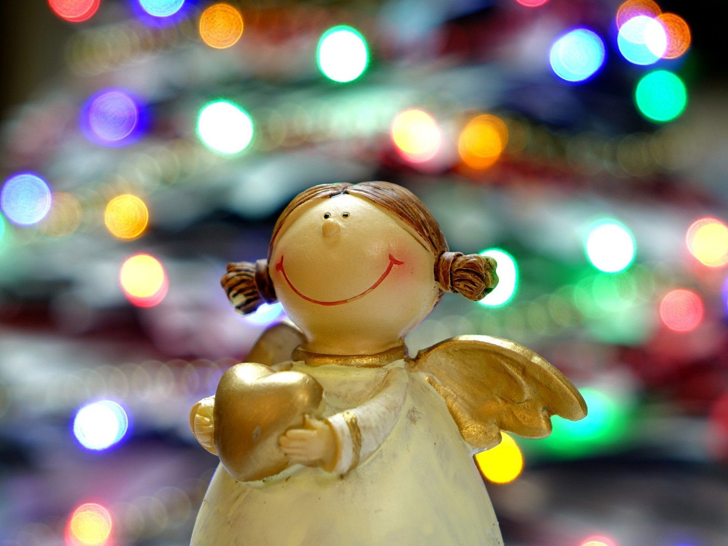 A small cherub angel decoration. The background is a blurred tree with lights.