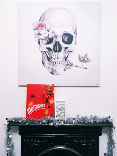 A photo of the fireplace in my bedroom. It's black against a white wall. On top of the fireplace is a length of silver tinsel and a Maltesers Christmas advent calendar. Above my fireplace is a large skull and rose canvas.