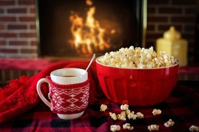 A fireside close-up of a mug of a hot drink and a red bowl of popcorn.