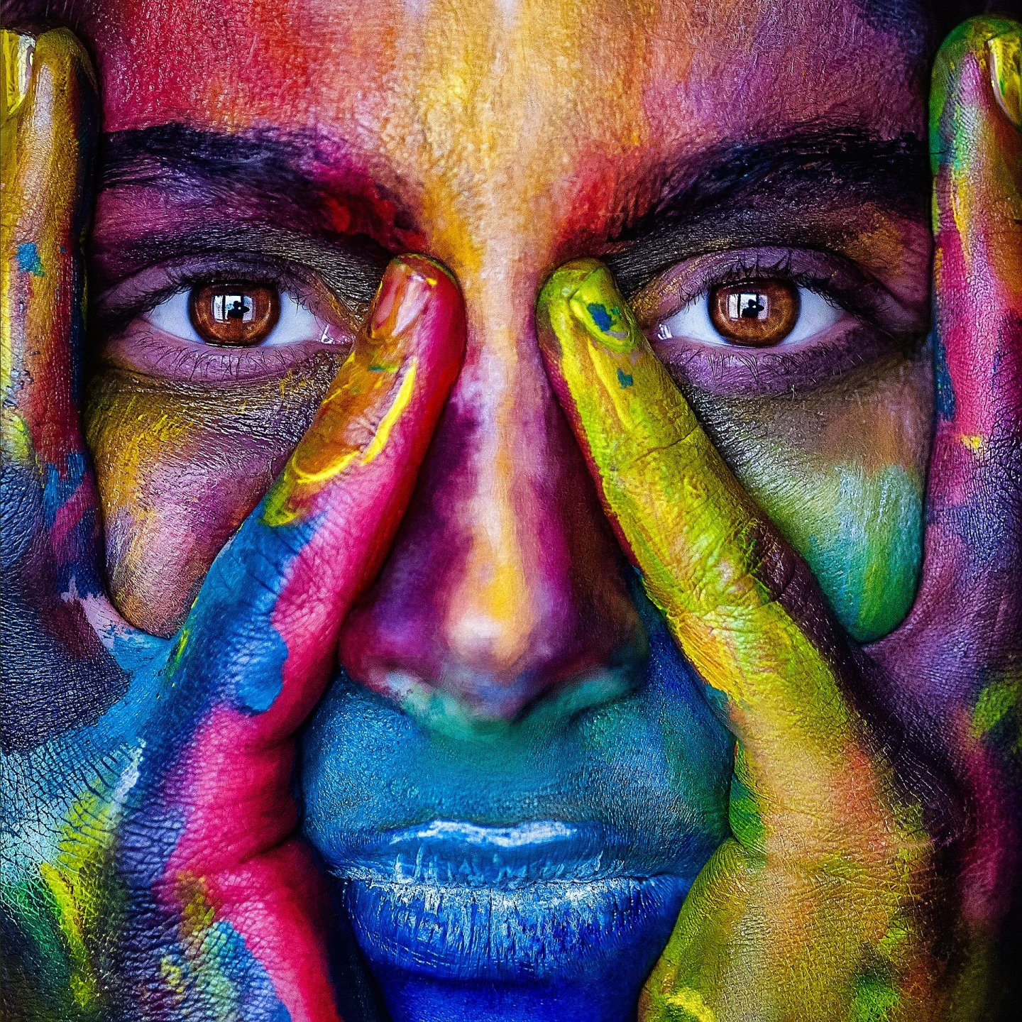 A close-up photo of a woman's face, with her hands played out around her eyes. She's covered in colourful paint.