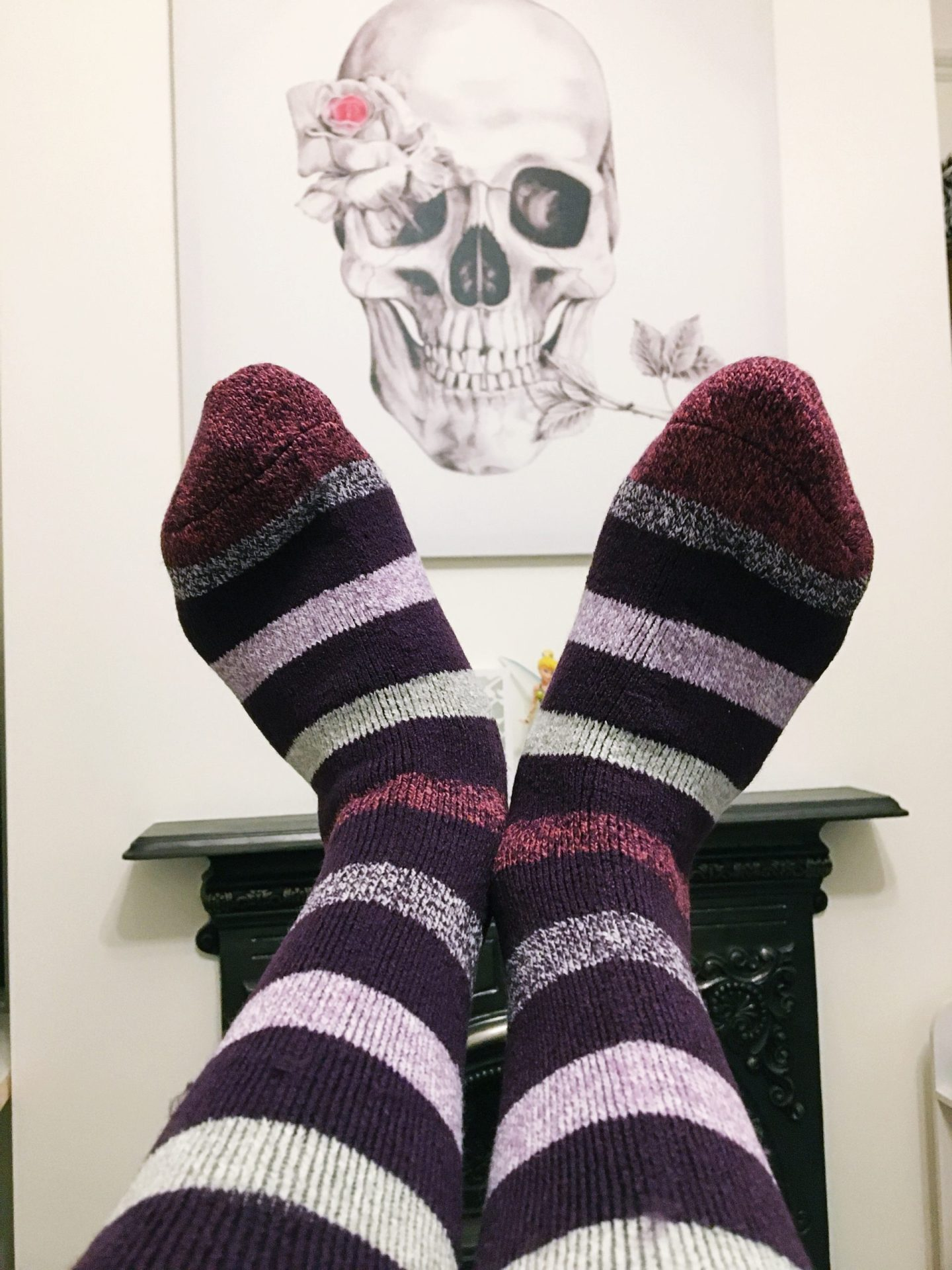 A photo of my legs out wearing the purple stripe socks with my fireplace and skull canvas in the background.