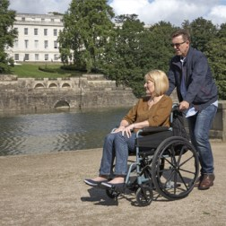 A woman in a wheelchair being pushed by a man. It looks like spring, and they're next to a small river and beyond that trees and a big white house or block of flats.