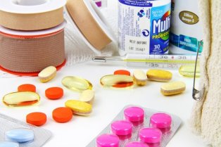A close-up photo of different medical supplies, with jars of multivitamins, a thermometer, and various colourful tablet medications on a white surface.