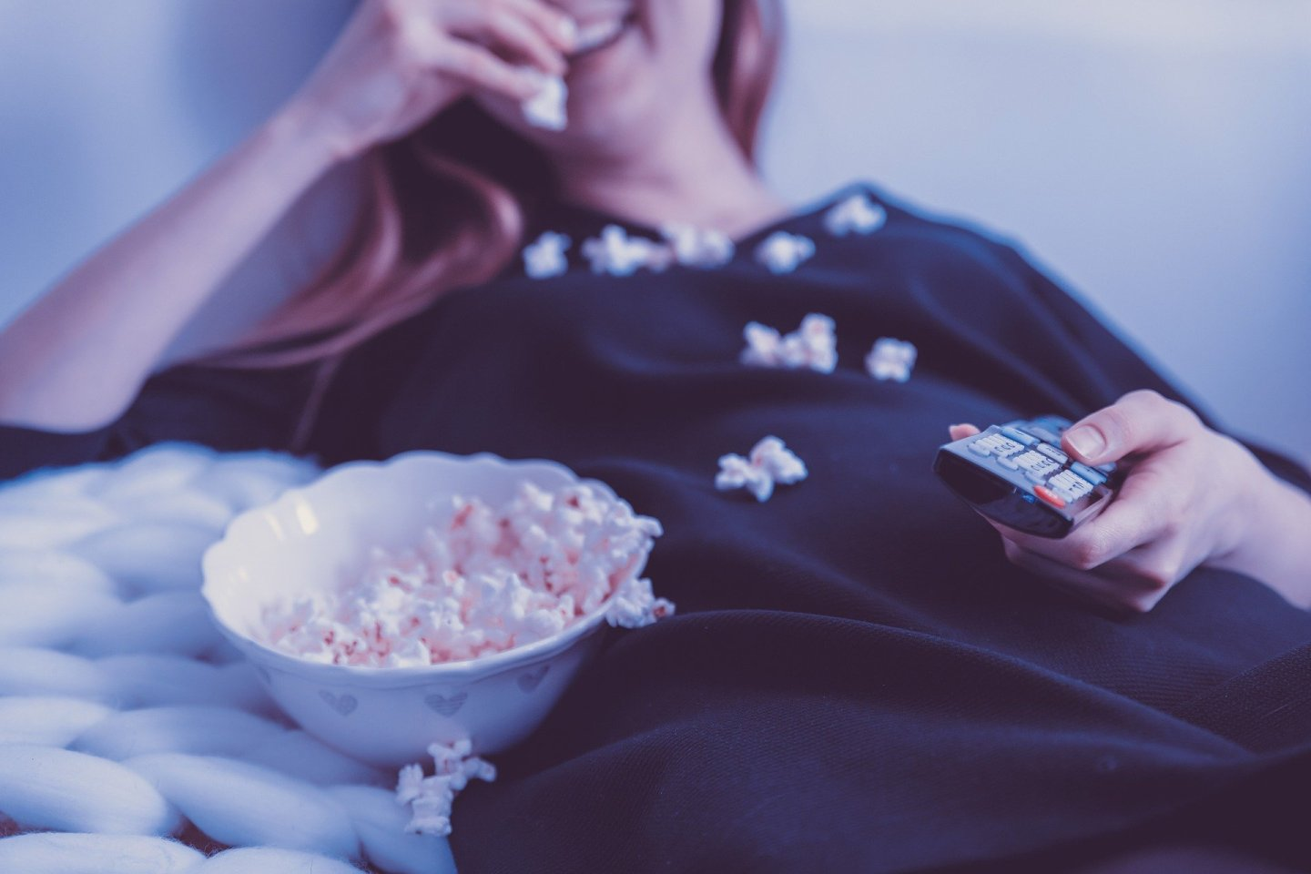 A woman smiling, holding a remote control watching the TV and eating popcorn, with popcorn all down her jumper.