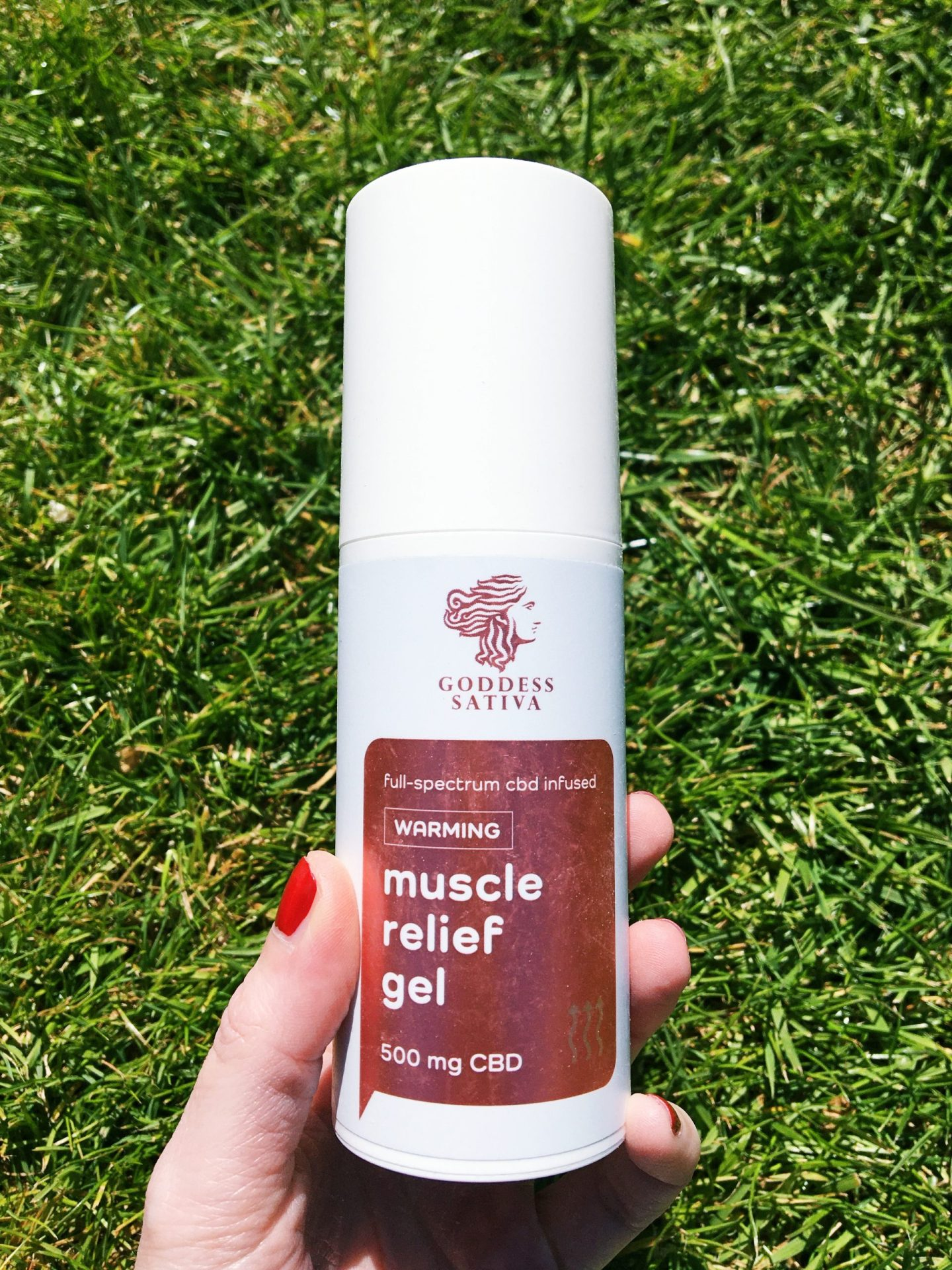 Me holding the muscle relief gel. It's a white bottle with a shiny pin label on the front.