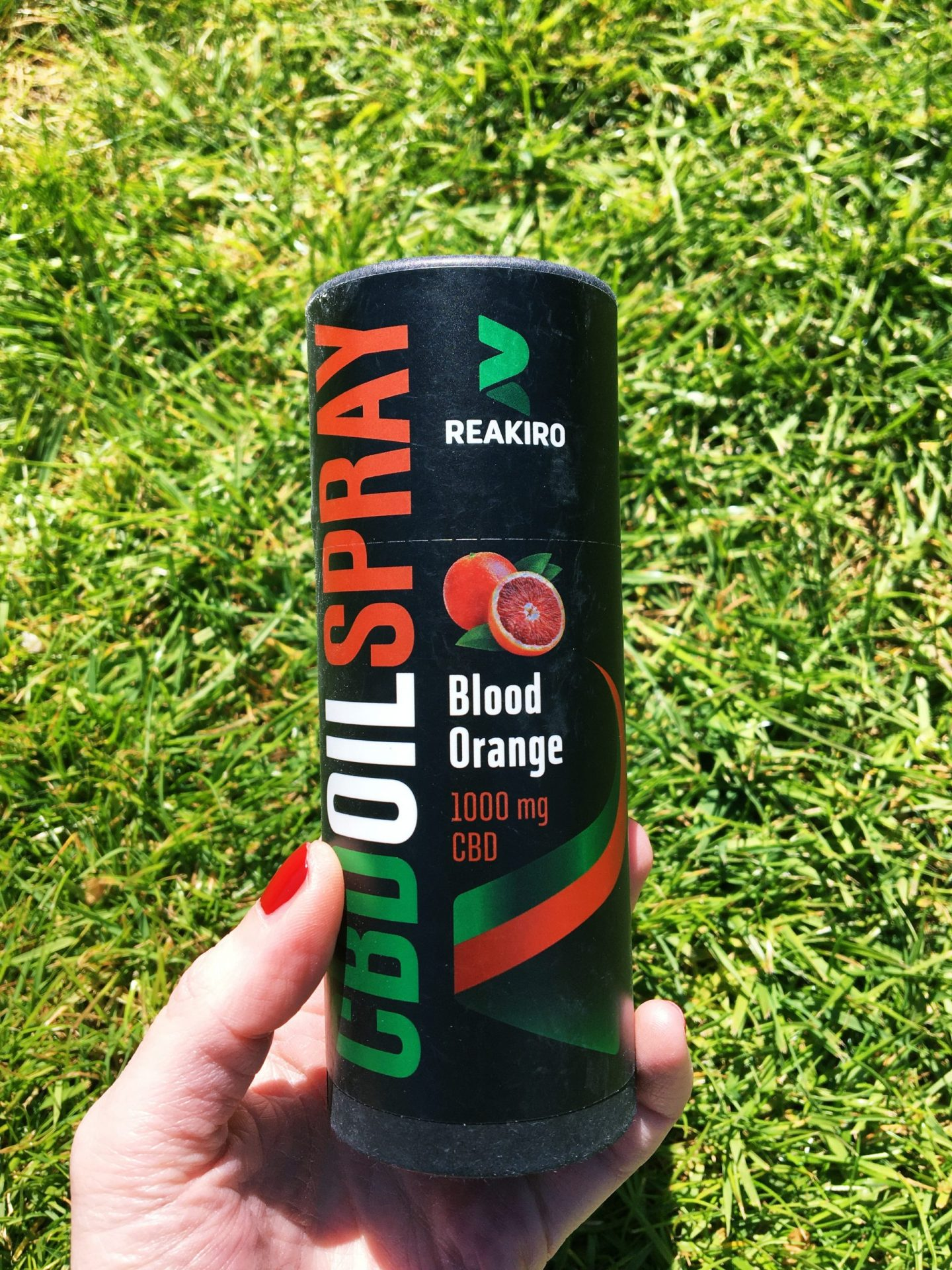 Me holding the oil spray. It's black and cylindrical, looking like a can of pop, with green, white and red designs for the text.