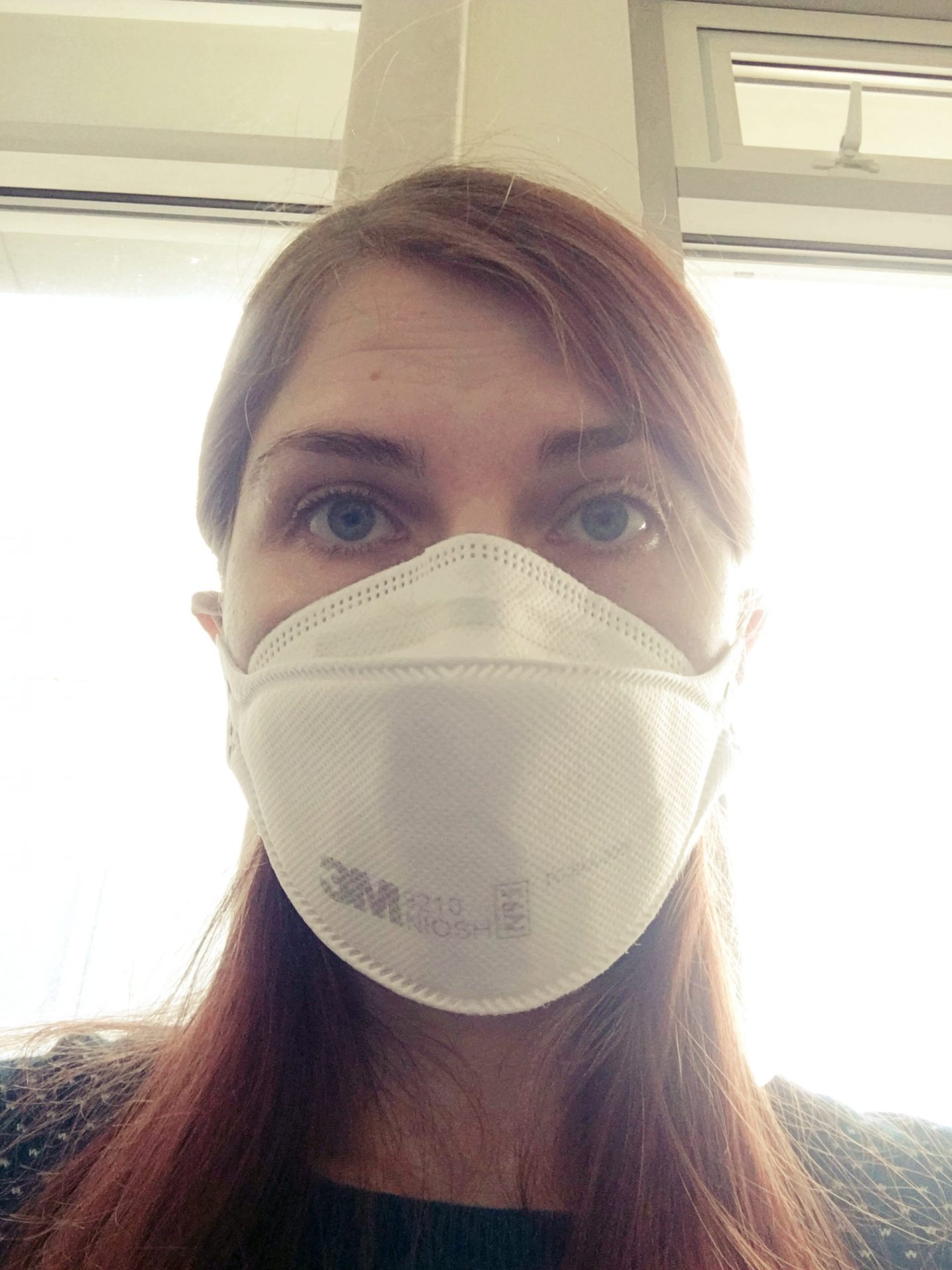 A head/shoulders photo of me in my mask waiting in the hospital, with the light from the window behind me.