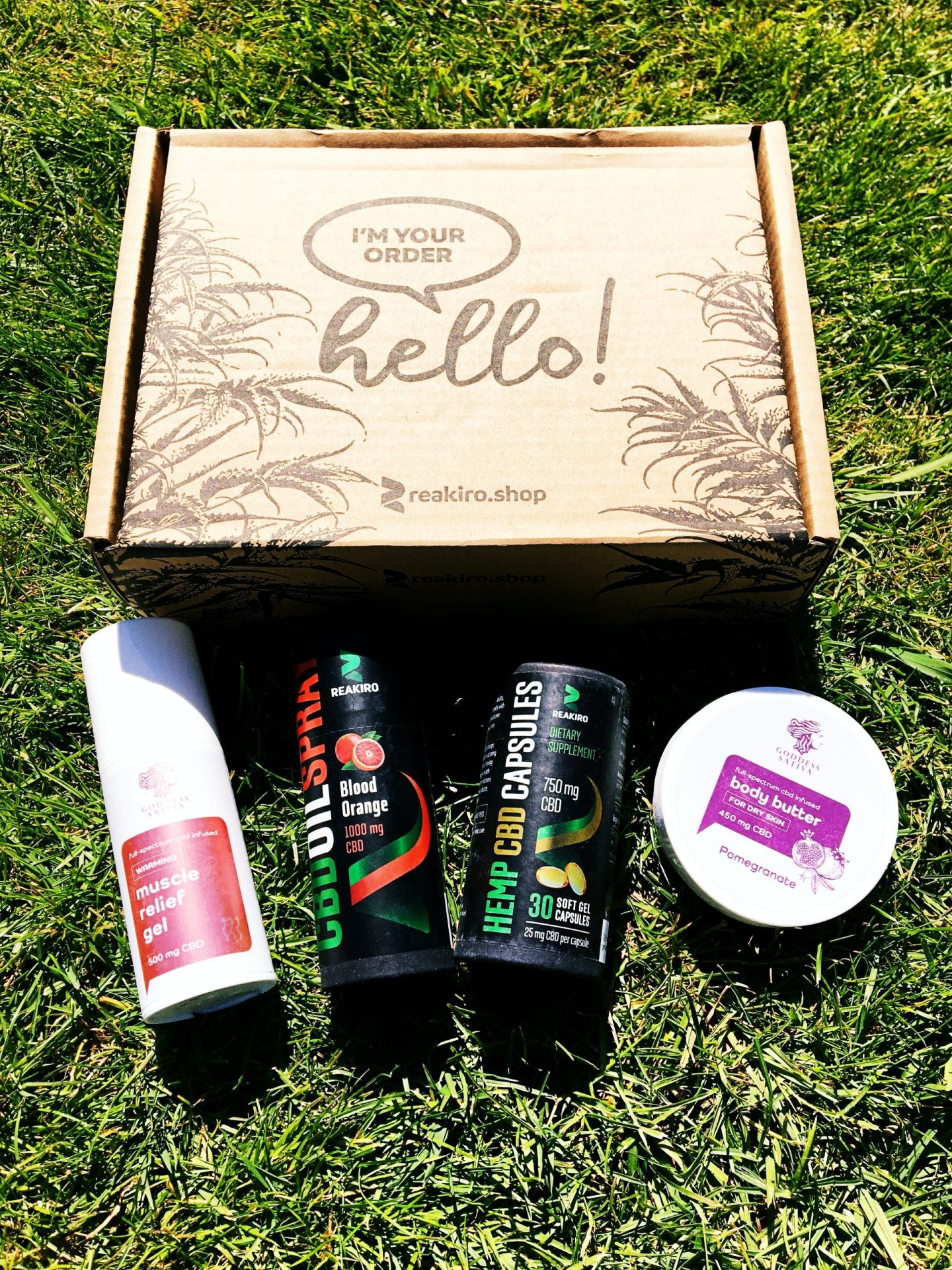 All four products laid out side by side on the grass in front, with the box they arrived in saying 'hello, I'm your order' behind them.