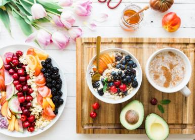 A colourful photo of fruits and veggies on a plate and in a bowel, with some flowers at the top to give it a bright and summery feel.