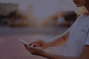 Invstr-girl-holding-iphone-white-t-shirt-sunset-v2