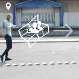 Eine Frau in einer grünen Bluse steht in einem asphaltiertem Hinterhof. Sie schaut auf eine Smart-Watch. Um die Frau herum sind verschiedene weiße Icons zu sehen, die symbolisieren, was die Smart-Watch anzeigt.