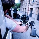 Der Kamera lehnt sich weit aus dem Auto um den Schauspieler auf seinem Roller im Bild zu haben