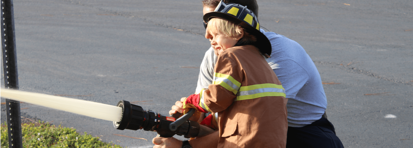 Firefighter assisting a child with a Fire Hose