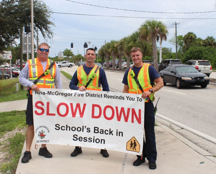 Firefighters holding sign: Slow Down - School's Back in Session