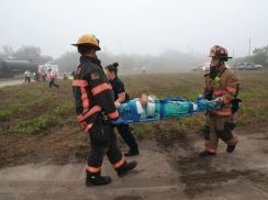 Two firefighters carrying a person on a stretcher
