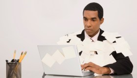 A businessman working on a laptop and covering with adhesive notes