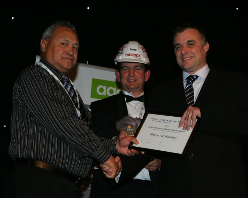 <strong>Hans Hollis</strong> Manager, Holcim Hastings Quarry receives the Winstone Aggregates Safety Trophy from Jason Lowe. Conference MC, Steve Davis look on