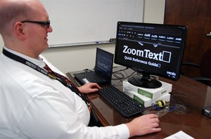 Man at computer reading a Zoom Text quick reference guide.