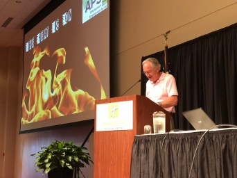 "Senator Harkin presenting his keynote, at a lecturn with a powerpoint seen behind that says ""Iowa APSE: The Heat is on!"""