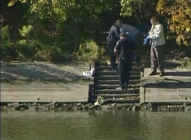 Officials retrieve body from river.