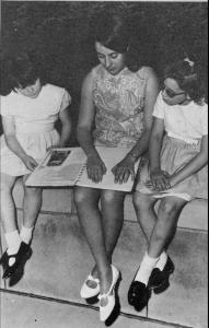 """""""A black-and-white photo showing a blind college student reading a print-Braille book while tutoring two young girls"""""""