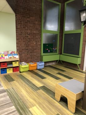 Picture of activity center in new youth library space.  Contains books, lego board and magnetic board.