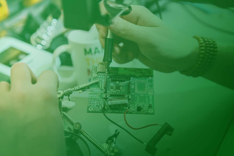 Zum Beitrag Elektronik Entwicklung: zwei Hände halten eine Platine und arbeiten an ihr