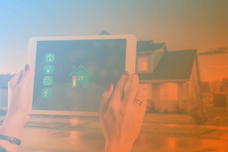 """Zum Artikel """"Sensoren: Wie sie funktionieren und wo sie eingesetzt werden"""": Tablet in Händen mit Smart Home Anwendung mit Dashboard zu Temperatursensor, Sicherheit, Energie, Haus im Hintergrund"""
