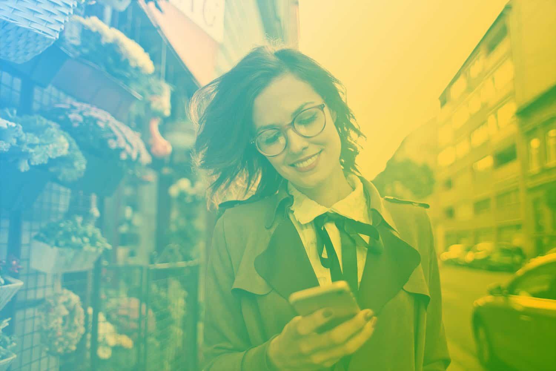 Zum Beitrag IoT im Handel - mit neuen Vertriebskanäle zum Handel 4.0: Frau mit Smartphone in der Hand vor Einkaufsladen an der Straße