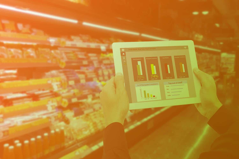 Zum Artikel IoT im Handel Use Cases: Tablet mit Warenbeständen in der Hand, im Hintergrund ein intelligentes Regal (Smart Shelf)