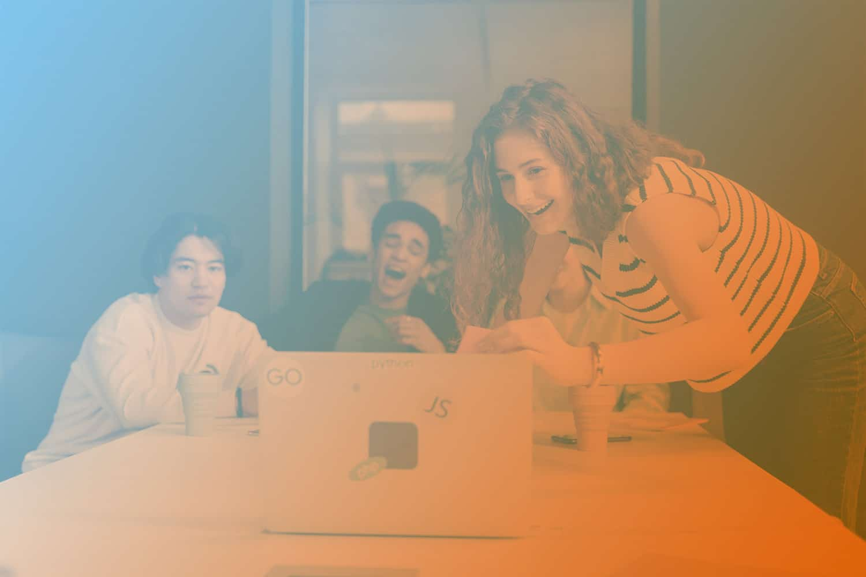 """Zum Beitrag """"Agile Produktentwicklung"""": Personen schauen sitzend und stehend lachend auf Laptop"""
