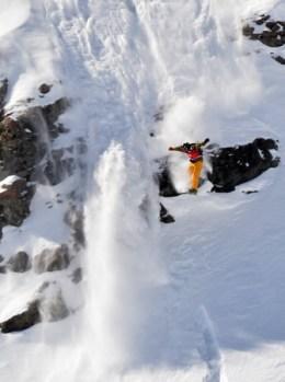 Snowboardeur sautant une barre