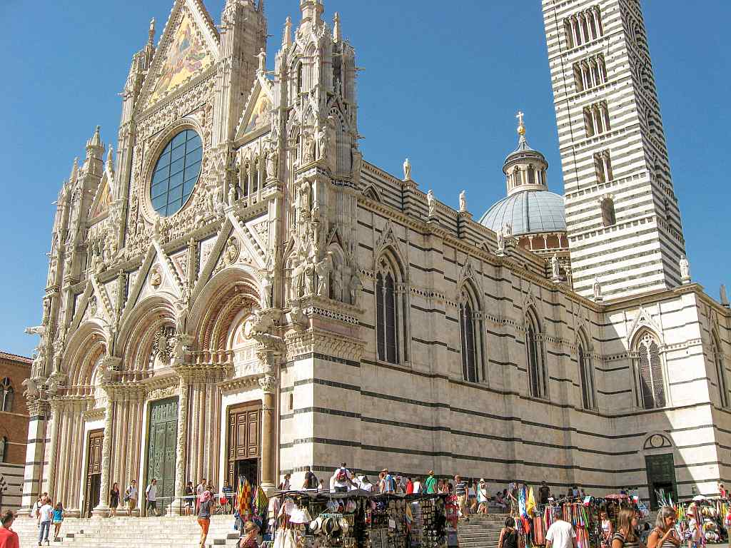 a cathedral of white, rose and black marmer with a beautiful intricate facade and a high bell tower, the cathedral in Siena