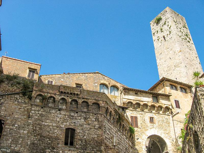 medieval houses and a medieval tower with a bright blue sky on the background, San Gimignano in Tuscany Italy
