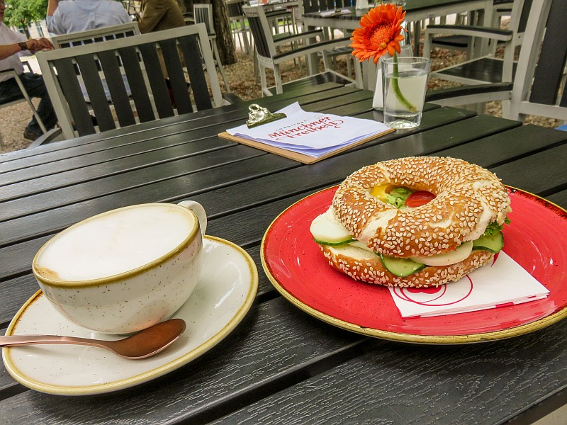 a cup of cappuccino and a bagel on a table, late lunch on the terrace of the cafe at the Pinakothek der Moderne