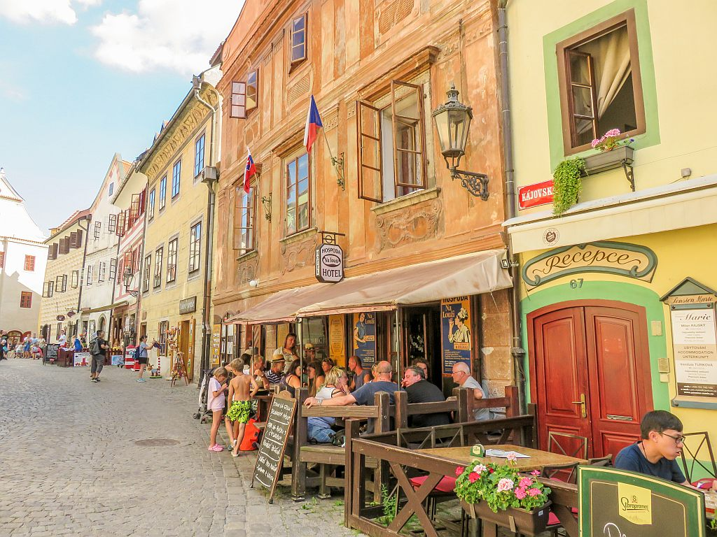colourful houses in yellow and orange with cafe terraces on the street and people sitting there, Cesky Krumlov in South Bohemia, Czech Republic