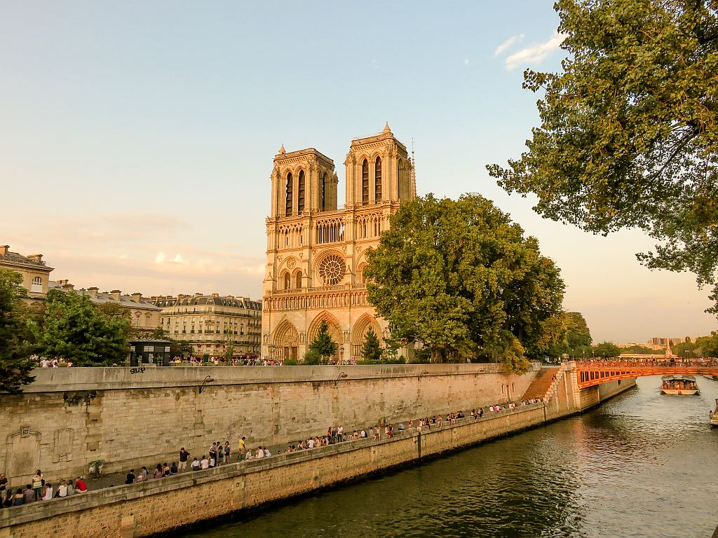 a river with a cathedral at the background during golden hour, Notre Dame du Paris at Paris, France
