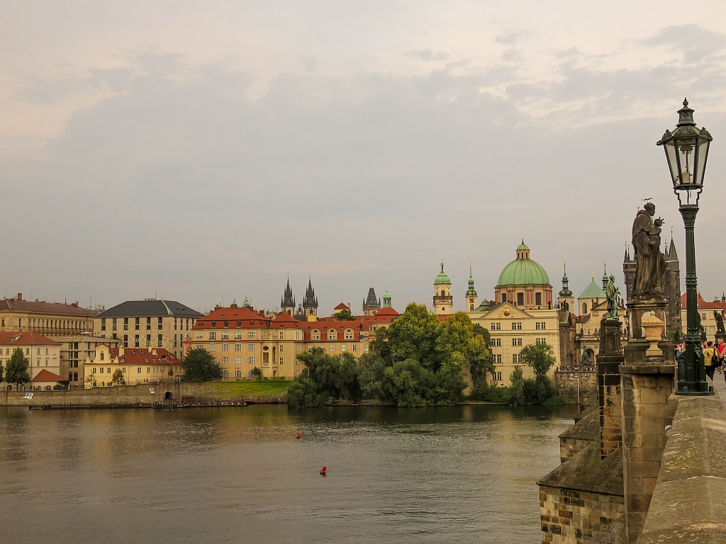 a river and a city at dusk with a bridge partly visible to the left, Prague in Czech Republic
