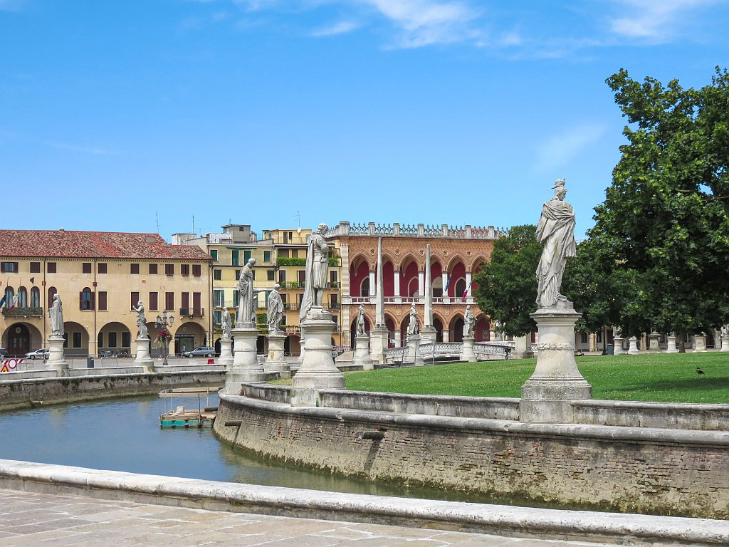 a water feature with statues around it and green in the middle with renaissance buildings at the background, Prato della Valle Square in Padua