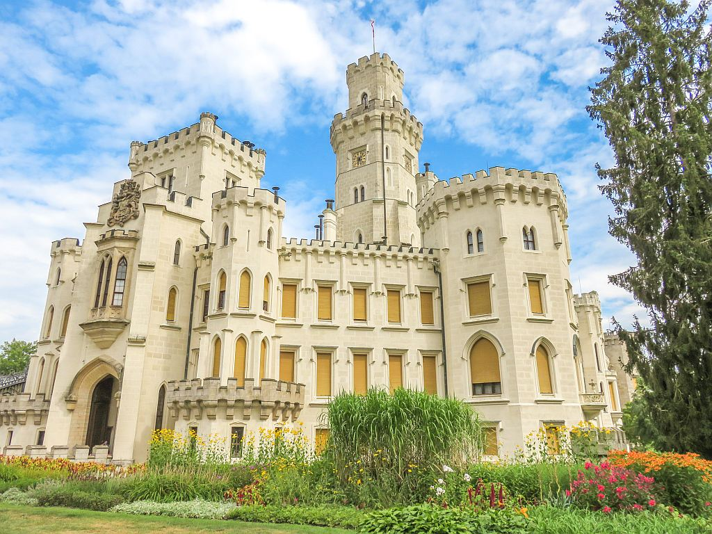a white castle against a blue sky with some beautiful flowers in front; Hluboka Castle in Czech Republic