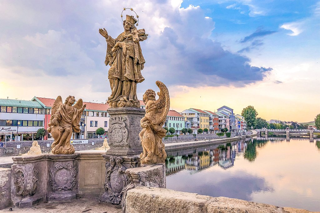 statues of a saint and 2 angels on a bridge above a river with colourful houses on the river bank and sunset with yellow and purple hues; the Old Bridge in Pisek