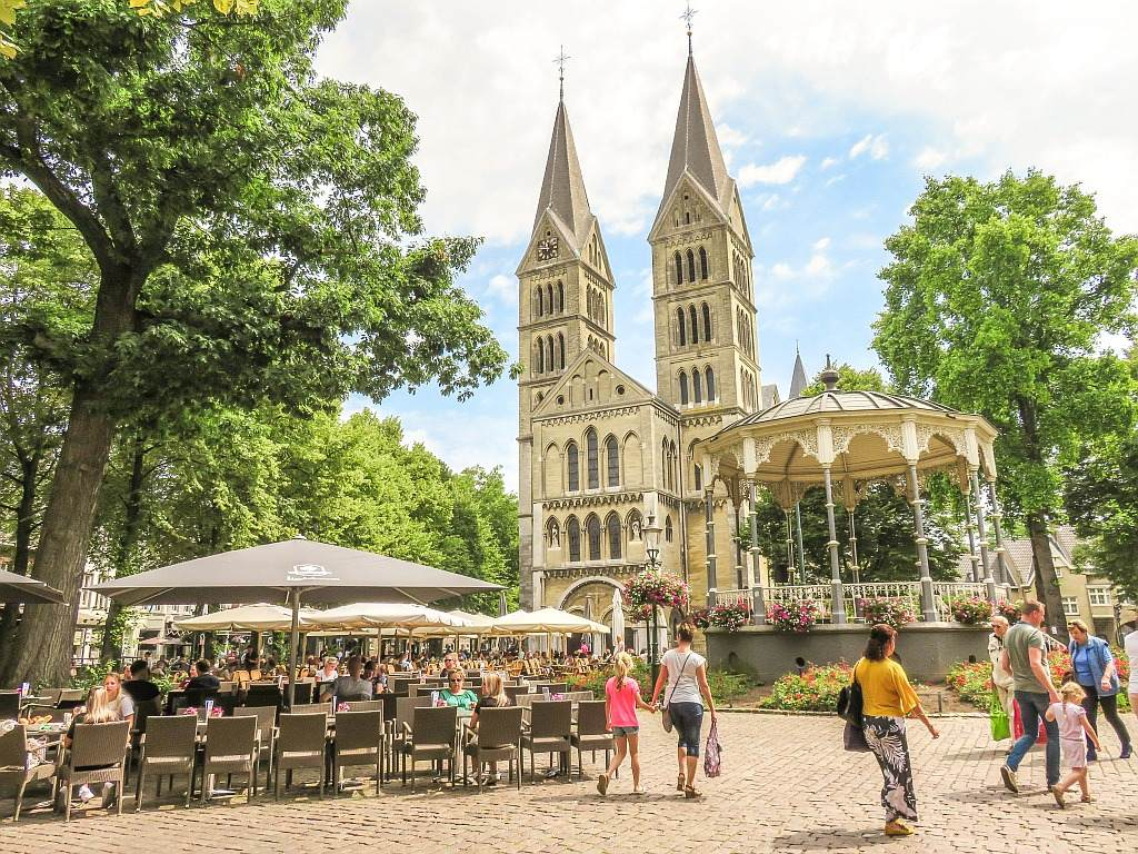 a church at the bottom with some cafes in front and people walking around and pavilion adorned with hanging flowers in pots; the Munster square in Roermond Limburg
