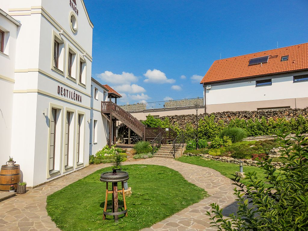 inner court with a white building and some green landscaping; the distillery of the Svachovka Complex