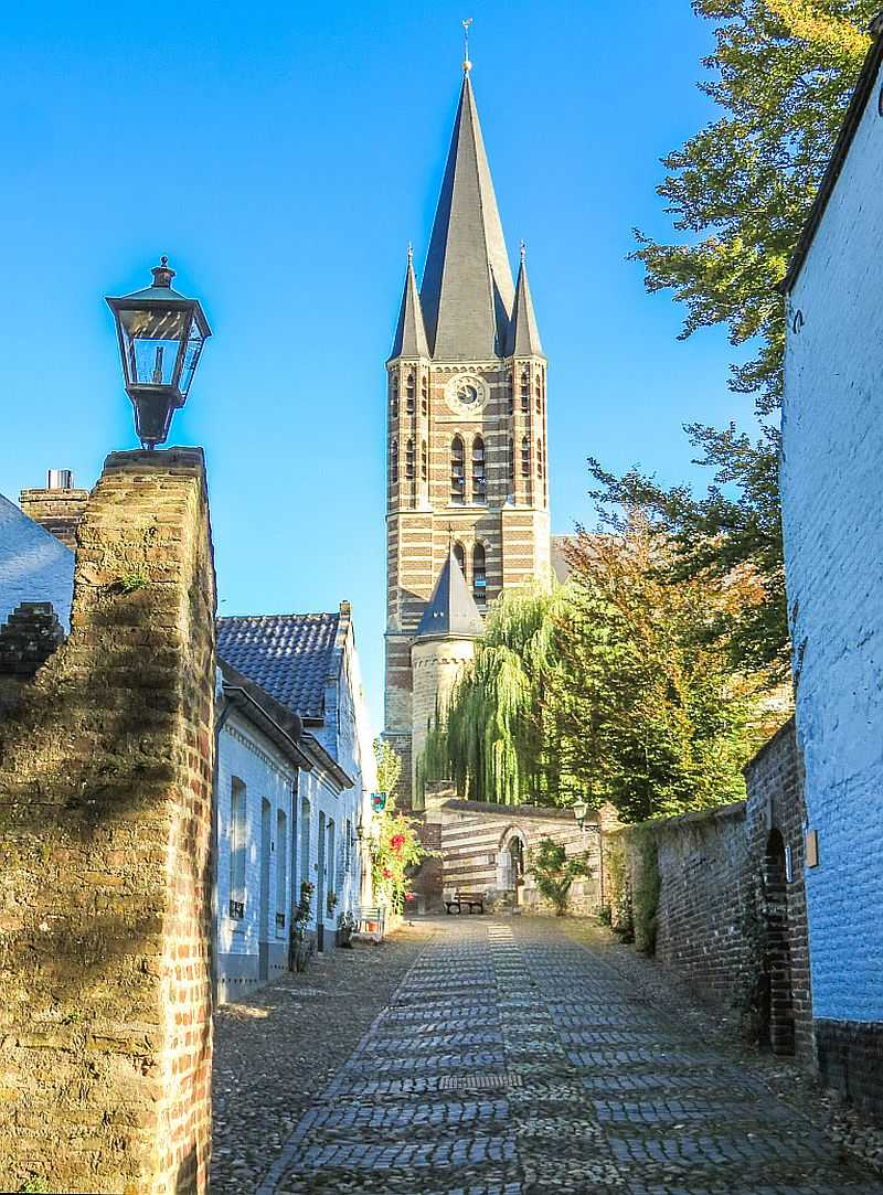 a cobblestone street going up a hill and at the end a church with high belfry, a lot of trees and blue sky