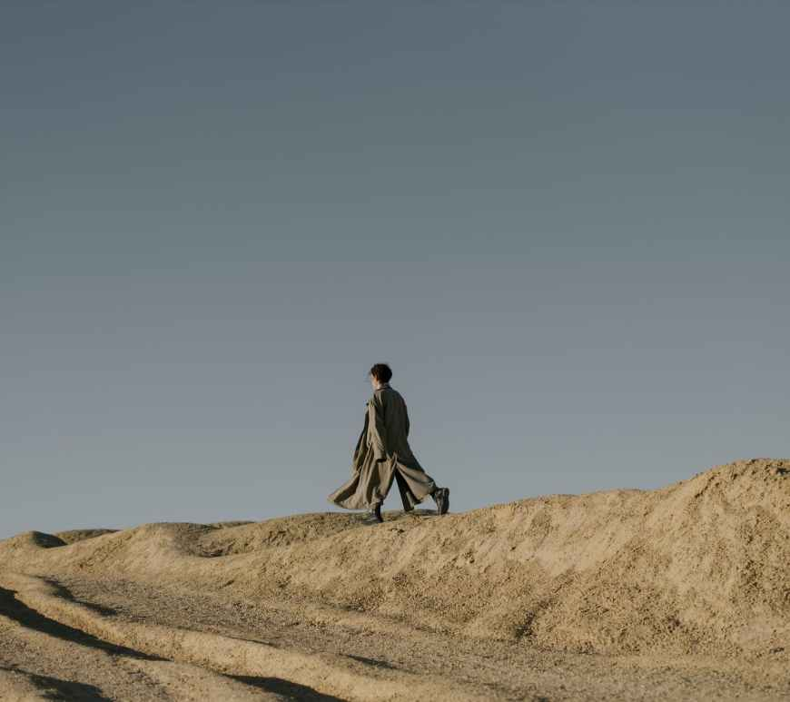 man in black jacket walking on brown sand
