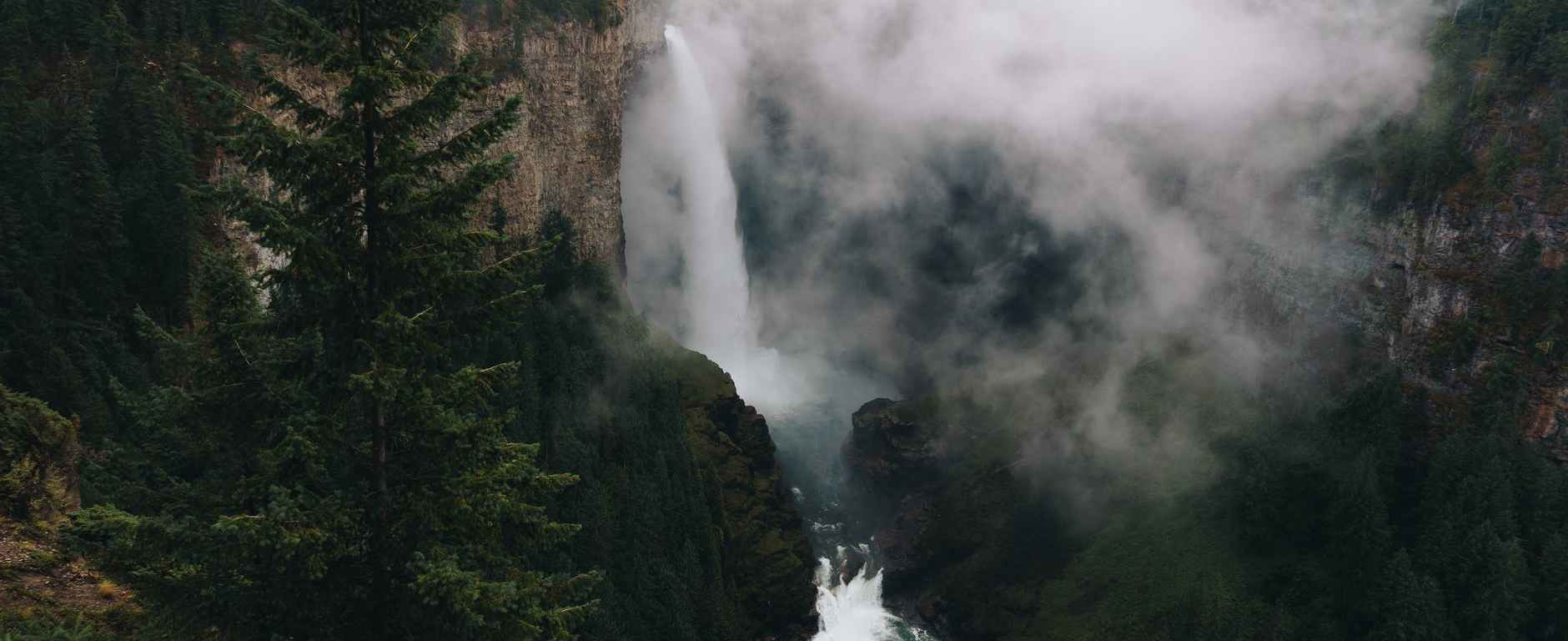 waterfall in mountainous terrain with evergreen forest against cloudy sky
