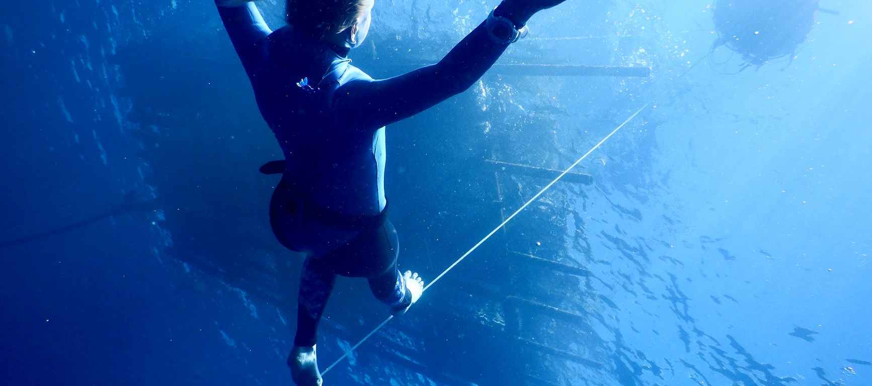 anonymous woman diving underwater of blue sea