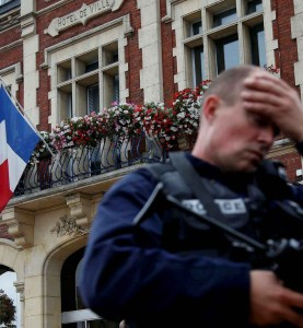 A policeman reacts as he secures a position in front of the city hall after two assailants had taken five people hostage in the church at Saint-Etienne-du -Rouvray near Rouen in Normandy, France, July 26, 2016. REUTERS/Pascal Rossignol