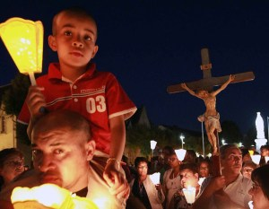 Pilgrims attend a candlelight procession for the virgin Mary at the sanctuary of Lourdes, southwestern France, Sunday Aug. 14, 2016. Security measures for Lourdes' biggest annual event, the Feast of the Assumption, has been increased as France, on edge with fears of a new terror attack, continues to cancel festive and sports events for security reasons. (AP Photo/Bob Edme)